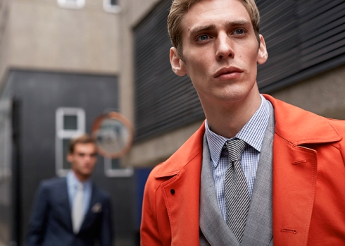 Fitzrovia: single-breasted burnt-orange cotton gabardine trench coat with a double-breasted light grey faded Prince of Wales Check peak-lapel suit, pale blue grid cotton shirt with semi-cutaway collar, navy stripe textured-silk tie and navy complicated diamond silk pocket square